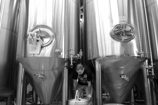 """Jordan """"Chardonnay"""" Wong fills a cask amidst the towering 3,000 litre stainless steel tanks."""