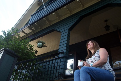 Photo by Mario Bartel Kathryn Matts enjoys a cup of coffee on the stoop of her 1912 Craftsman house across from Moody Park. The house is being featured in this year's 36th annual Heritage Homes tour to be held May 29.
