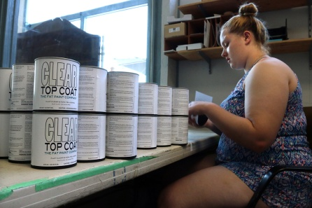 PHOTO BY MARIO BARTEL Shelby Mattin-Abbott glues labels to cans at The FAT Paint Company's 3,065 square foot production facility in an old converted auto repair garage.