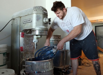 PHOTO BY MARIO BARTEL Jamie Wandell combines the chalk and paint in a old industrial bread mixer. The FAT Paint Company recently upgraded to a more automated mixing process to keep up with the demand for its paint. Wandell has moved to Regina to study and play football at the University of Regina.