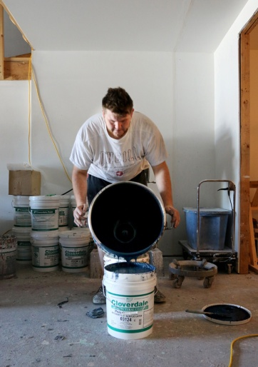 PHOTO BY MARIO BARTEL Jamie Wandell pours a freshly-mixed batch of FAT Paint into a drum. The ratio of chalk to paint varies with each colour.