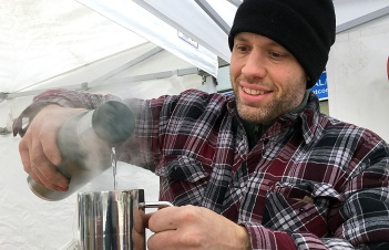 Aaron pours a steaming mug of tea to stay warm in the Ossome Acres booth.