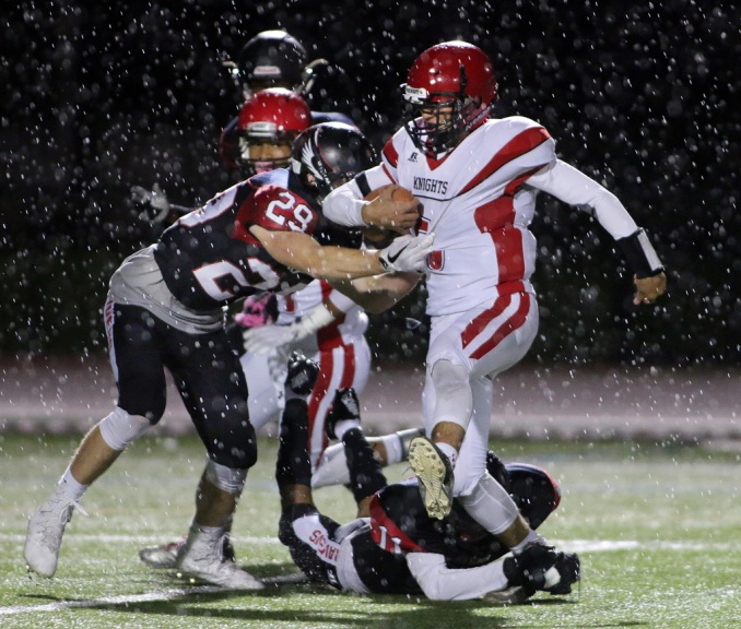 A rainstorm and backlight can turn a routine shot of football action into something epic.
