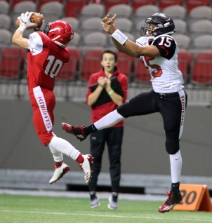 Normally I scan right past photos with unexpected and unexplained random people in the background. But the surprised look on the sideline spectator's face just adds to this shot of an interception.