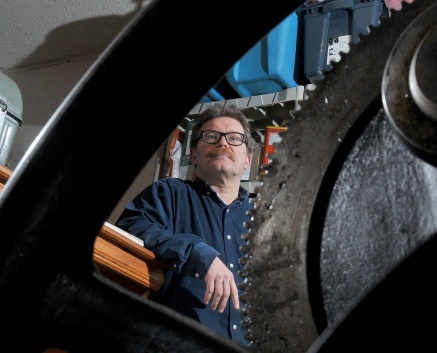 MARIO BARTEL/THE TRI-CITY NEWS Port Moody graphic artist Markus Fahrner is framed by the flywheel of his vintage 1914 Colt Armoury letterpress.