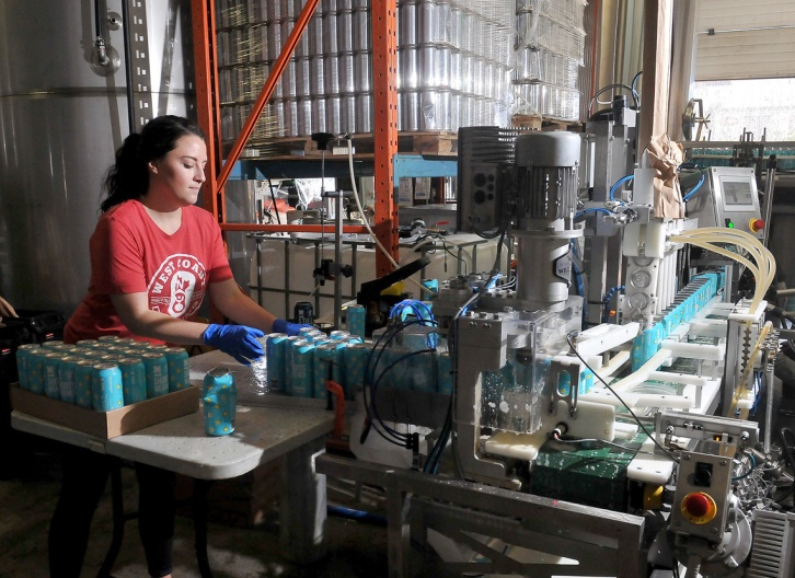 MARIO BARTEL/THE TRI-CITY NEWS Ali Makin sorts cans at the end of one of two portable canning lines set up Monday at Moody Ales to package the brewery's new collaboration beer with West Coast Canning.