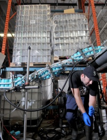 MARIO BARTEL/THE TRI-CITY NEWS Bob Maguire ducks under the canning line.