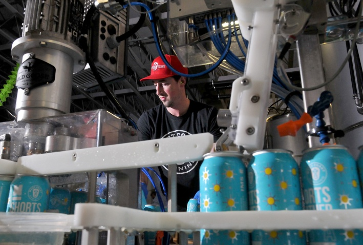 MARIO BARTEL/THE TRI-CITY NEWS Matt Leslie pulls filled cans off the end of one of two portable canning lines running at Moody Ales on Monday to package their new collaboration beers with West Coast Canning that will help raise money for KidSports Tri-Cities.