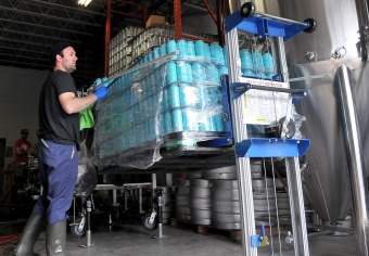 MARIO BARTEL/THE TRI-CITY NEWS Bob Maguire lines up cans for loading into the canning line.