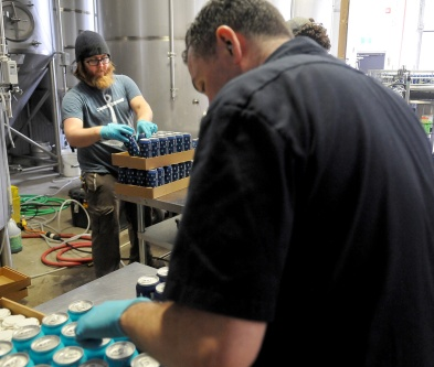 MARIO BARTEL/THE TRI-CITY NEWS It's all hands on deck in a team effort to can and sort two new beers that have been collaboratively created by Moody Ales and West Coast Canning to help raise money for Kidsport Tri-Cities.
