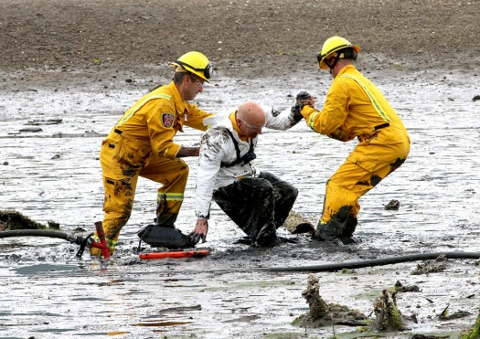 "MARIO BARTEL/THE TRI-CITY NEWS Port Moody fire caption Rob Suzukovich gets some help back on his feet from his ""rescuers,"" firefighters Darren Penner and Jason Webster, during a training exercise to extricate people trapped in the mudflats at the east end of Port Moody Inlet."