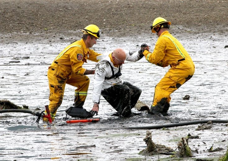 """MARIO BARTEL/THE TRI-CITY NEWS Port Moody fire caption Rob Suzukovich gets some help back on his feet from his """"rescuers,"""" firefighters Darren Penner and Jason Webster, during a training exercise to extricate people trapped in the mudflats at the east end of Port Moody Inlet."""