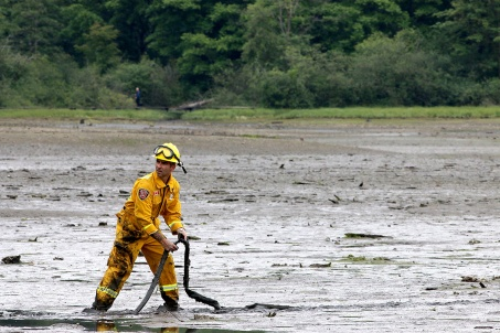 MARIO BARTEL/THE TRI-CITY NEWS A Port Moody firefighter deploys a 1.25-inch hose attached to a high-pressure spray gun that can be used to loosen the mud around a victim trapped in the mudflats at the eastern end of Port Moody Inlet.