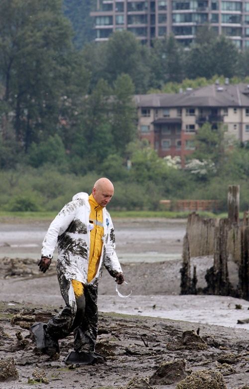 """MARIO BARTEL/THE TRI-CITY NEWS Muddy but otherwise unhurt, Ron Suzukovich heads for solid ground after serving as the """"victim"""" in a training exercise to help Port Moody firefighters rescue people trapped in the mudflats at the eastern end of Port Moody Inlet."""
