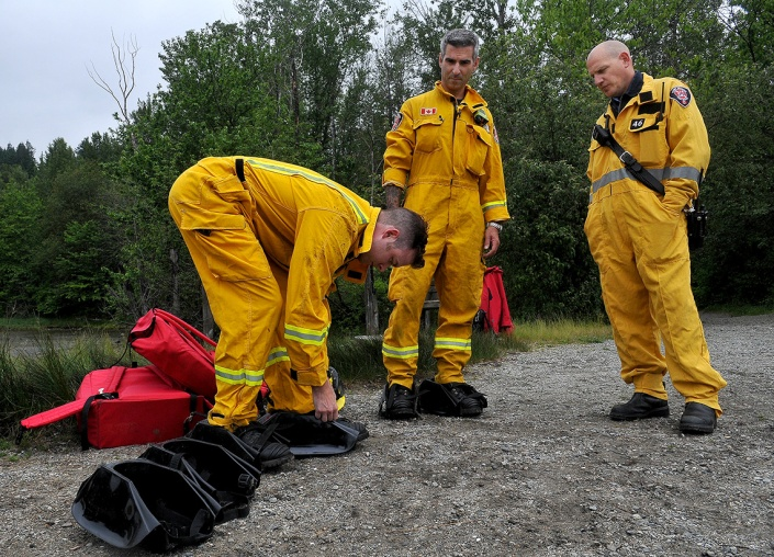 MARIO BARTEL/THE TRI-CITY NEWS Port Moody firefighters strap on special plastic overshoes that allow them to walk on the surface of the mudflats to rescue people stuck in the muck.