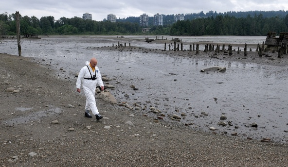 """MARIO BARTEL/THE TRI-CITY NEWS The designated """"victim"""" for the exercise, Port Moody fire captain Ron Suzukovich, walks toward his doom in the mudflats off the Old Mill site on the north shore of Port Moody Inlet. Fire chief Ron Coulson says the easy access to the flats from shoreline trails and the proximity of many residents means his crews usually get called out twice a year to pluck people from the heavy muck."""