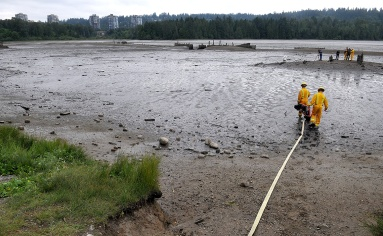 MARIO BARTEL/THE TRI-CITY NEWS Wearing special overshoes that allow them to walk on the mud, Port Moody firefighters Darren Penner and Jason Webster head out to rescue their trapped colleague.