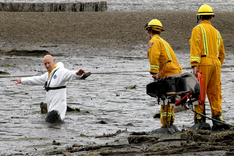 MARIO BARTEL/THE TRI-CITY NEWS After hiking across the mudflat in their special overshoes, Port Moody firefighters Darren Penner and Jason Webster arrive at their stuck colleague, Rob Suzukovich.