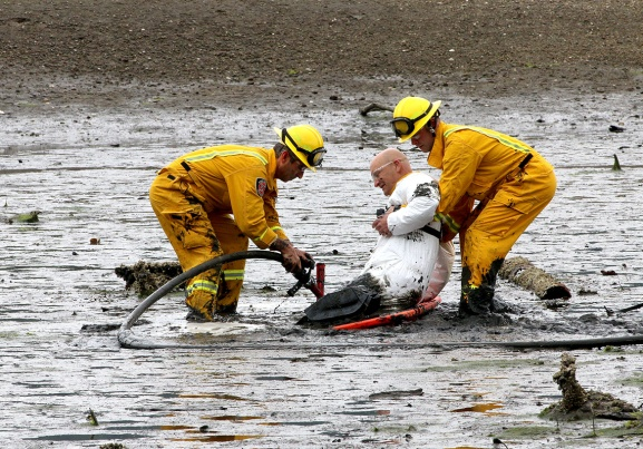 "MARIO BARTEL/THE TRI-CITY NEWS Port Moody firefighters use a high-pressure spray gun to loosen the mud around their ""victim"" so he can be pulled to a spinal board to strap on special overshoes that will allow him to walk back to firmer terrain."