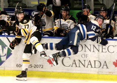 MARIO BARTEL/THE TRI-CITY NEWS Langley Rivermen forward Tanner Versluis gets checked into the Coquitlam Express bench by Chase Danol in the first period of their BC Hockey League game, Wednesday at the Poirier Sports and Leisure Complex.