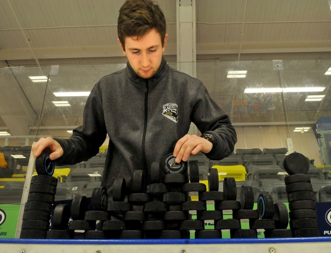 MARIO BARTEL/THE TRI-CITY NEWS Couqitlam Express trainer Russ Maceluch carefully stacks pucks the team's players will use during their pre-game warmup.