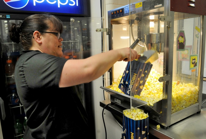 MARIO BARTEL/THE TRI-CITY NEWS Concession attendant Sonya Folster begins loading up bags of popcorn in anticipation of a crowd of young people as students from several schools are expected to attend Wednesday's midday game.