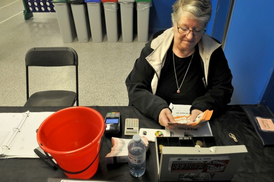 MARIO BARTEL/THE TRI-CITY NEWS Volunteer ticket seller Yvonne Kiraly counts tickets prior to the doors opening for Wednesday's midday game against the Langley Rivermen. She said she's been helping out since last year.