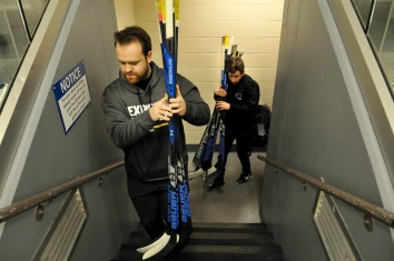 MARIO BARTEL/THE TRI-CITY NEWS Team chiropractor Harrison Wagner and trainer Russ Maceluch deliver the players' sticks to the bench.