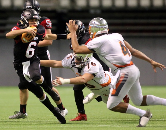 MARIO BARTEL/THE TRI-CITY NEWS Terry Fox Ravens quarterback Key'Shaun Dorsey tries to escape from New Westminster Hyacks tacklers Kinsale Phillip and Evan Nolli in their BC Secondary Schools Football Association AAA semi-final, Saturday at BC Place Stadium. New Westminster won the game, 33-0.