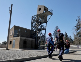 MARIO BARTEL/THE TRI-CITY NEWS The squad walks to the training tower where they'll spend the afternoon learning how to tie special knots and set up safety and main lines so they can rappel back down to the ground.