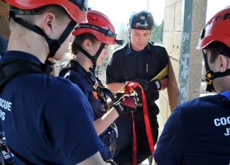 MARIO BARTEL/THE TRI-CITY NEWS Atop the tower, the students pay close attention to the details of tying knots that will secure safety lines for their descent.