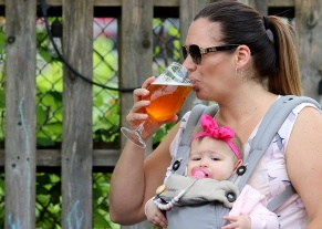 MARIO BARTEL/THE TRI-CITY NEWS Carly Somner enjoys a beer accompanied by her seven-month-old daughter, Lucy.