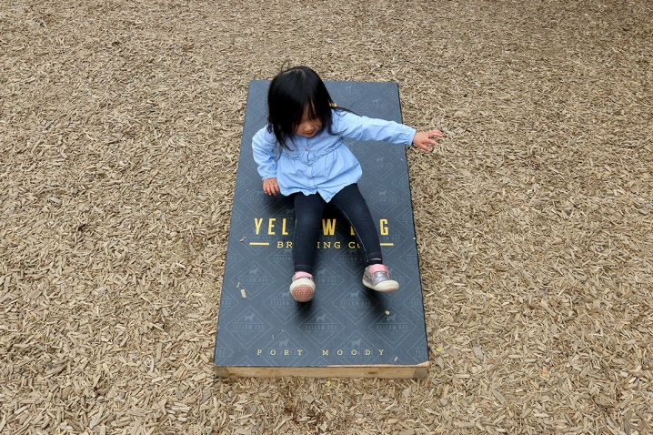 MARIO BARTEL/THE TRI-CITY NEWS Olivia Ong, 2, turns a cornhole board into an impromptu slide at the monthly gathering of the Tri-Cities Babies and Beer meetup group at Yellow Dog Brewing in Port Moody.