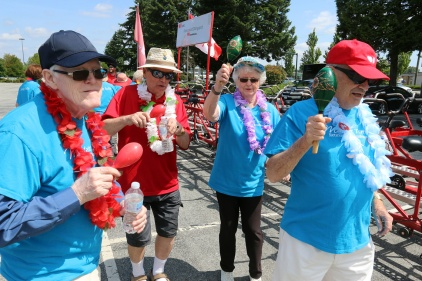 """MARIO BARTEL/THE TRI-CITY NEWS Brian and Barb Corbould, right, lead some of their team members from Mayfair retirement home, in a little warm-up dance prior to embarking on a ride on the Heart and Stroke Foundation's """"big bike."""""""