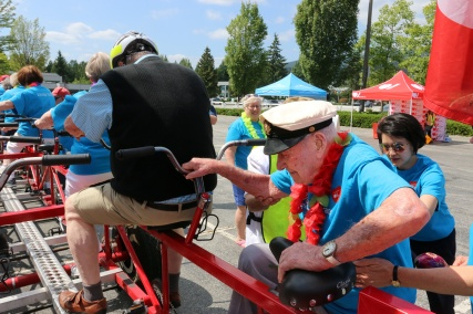 MARIO BARTEL/THE TRI-CITY NEWS Don Simpson, 106, gets a little help climbing aboard the big bike.