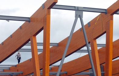 "MARIO BARTEL/THE TRI-CITY NEWS A worker is dwarfed by giant wooden beams at the new PoCo Recreation Complex that is underconstruction on Wilson Avenue. Back in the day when newspapers actually employed staff photographers who spent their whole shift doing just that, we'd often use downtime between assignments to check out things we'd spot in our travels that might make a good photo. Sometimes those photos — we called them ""wild art"" or ""tour shots"" would end up on the front page, and sometimes they'd help an editor plug a quarter-page hole deep in the paper. I made note of these magnificent beams being lifted into place at the new Port Coquitlam Community Centre, then did something about it when we did a construction update story."
