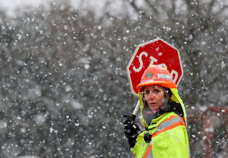 MARIO BARTEL/THE TRI-CITY NEWS Llyn Lindo, a traffic controller on Kingsway Avenue at the site of the new Port Coquitlam recreation complex, said she loves the snow, but the sign she's holding seems to sum up the thoughts of most people as a snow squall rolls through Thursday morning. It's March and it's snowing, just when everybody is thinking about spring. The key to capturing good snowfall photos is a dark background.