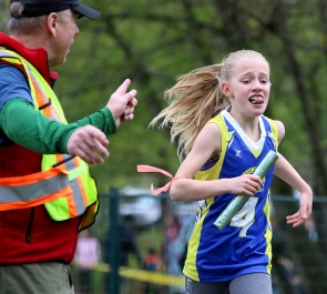 MARIO BARTEL/THE TRI-CITY NEWS Keira Cameron, from Ranch Park elementary school, is directed to victory in the Grade 4 girls race on the opening day of the 41st annual Como Lake Relays last Wednesday in Coquitlam. The Como Lake Relays is always a fun event to shoot as the kids are so determined and earnest in their efforts to do well for their school.