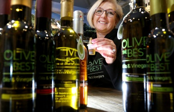 MARIO BARTEL/THE TRI-CITY NEWS Daniela Hammond samples one of the 60 or so olive oils and balsamic vinegars she offers at her new olive oil dispensary in Port Moody's Newport Village. Popping light through bottles is a fun way to bring a shot to life.