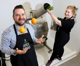 MARIO BARTEL/THE TRI-CITY NEWS Callan Morrison juggles oranges while his fiancé and business partner, Jessica Clark, loads the commercial juice presser that is installed in a custom shower enclosure at the back of their new Port Coquitlam juicery, Squish Juicery. The enclosure allows for quick and thorough cleaning of the juicer between pressings. Making juice from a large, industrial squeezer is not the most photogenic activity. But when that juicer is positioned in a huge shower stall and the subject is willing to play along with your suggestion to juggle, the result is a fun photo.