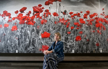 MARIO BARTEL/THE TRI-CITY NEWS Wendy Swalwell, the chair of Port Moody Legion's property development committee, admires the new branch on Clarke Street from its stage. As a background for a photo, the interior of the new Port Moody Legion is rather uninspiring. Except for the giant mural of a poppy field.