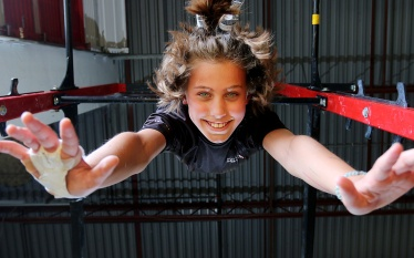 MARIO BARTEL/THE TRI-CITY NEWS Danika Michelsen hangs from a high bar at the Momentum Ninja Training Centre in Port Coquitlam. She's one of 36 athletes from the gym who've qualified to compete at the Ultimate Ninja Athletic Association world championships in Minnesota in July. This local Ninja gym is chock-a-block with climbing walls and other apparatus that can quickly overwhelm a photographer, let alone create busy backgrounds. That's when it's best to keep things simple.