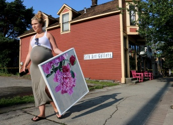 MARIO BARTEL/THE TRI-CITY NEWS Carola Alder, of CityState Consulting, that shares space in The Silk Gallery, removes one of the paintings left behind when two neighbouring buildings on Port Moody's Clarke Street caught fire Sunday night. The gallery, which is run by Coun. Zoe Royer, sustained smoke and water damage but most of its contents were safely removed to a nearby storage container. It's been years since many newspapers had the ability to monitor fire and police radios, but often the human storytelling shots of a disaster happen after the fact, as people try to understand and deal with their loss.