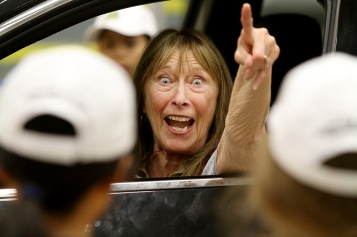 "MARIO BARTEL/THE TRI-CITY NEWS Wendy Yates, playing a suspected impaired driver, tells ""officers"" to give her more space during a simulated traffic stop at Coquitlam RCMP's Junior Mounties camp, last Wednesday at the Poirier Sport and Leisure Complex. This year's RCMP Junior Mounties camp changed the script from the usual obstacle course around the mezzanine at the Poirier Sport and Leisure Complex, but what's not to love about the animated expression of a volunteer playing a suspected impaired driver."