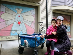 MARIO BARTEL/THE TRI-CITY NEWS Ladawne Shelstad and her daughter, Maddyn, 6, show off two of the chalk murals they designed and coloured on garage doors in their Klahanie neighbourhood to help brighten spirits during the COVID-19 lockdown. Their effort also inspired other neighbours to commission murals or design their own for their garage doors so now there's more than a dozen completed.