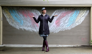 """MARIO BARTEL/THE TRI-CITY NEWS Ladawne Shelstad poses with one of her first """"interactive"""" chalk murals she's created for garage doors in her Klahanie neighbourhood in Port Moody to help brighten spirit during the COVID-19 lockdown."""