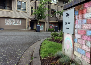 MARIO BARTEL/THE TRI-CITY NEWS Even the bricks at the entrance to Ladawne Shelstad's lane in the Klahanie neighbourhood have been chalked to create a colourful entrance to the gallery of garage doors decorated with chalk murals she designed, along with some of her neighbours.