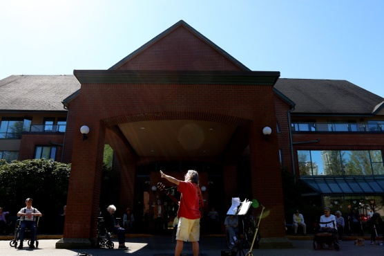 Chris Ridout often conducts his yoga and sing-a-long sessions for seniors from outside the common area at Parkwood Manor in Coquitlam. But last Thursday's warm weather brought everyone outside. Photograph By MARIO BARTEL/THE TRI-CITY NEWS