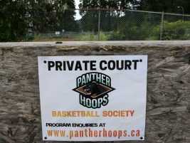 MARIO BARTEL/THE TRI-CITY NEWS A crooked fibreboard wall, an overgrown gully and a rusted, broken chainlink fence are the backdrop to one of the outdoor basketball courts installed in a parking lot behind BC Christain Academy in Coquitlam.
