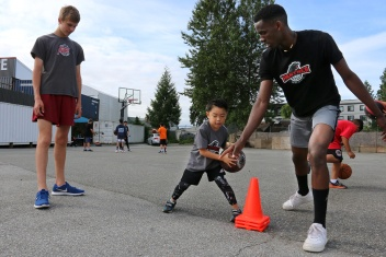 MARIO BARTEL/THE TRI-CITY NEWS David Mutabzi, right, works with one of his young charges, Skyler Nuestro, at Panther Hoops basketball camp.